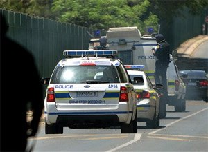 A vehicle believed to be transporting Oscar Pistorius, with police officers hanging on the sides, arrives at the Kgosi Mampuru Correctional Services prison in Pretoria, South Africa, Tuesday, Oct. 21, 2014. Pistorius was sentenced to five years imprisonment by judge Thokozile Masipais for killing his girlfriend Reeva Steenkamp last year. (AP Photo)