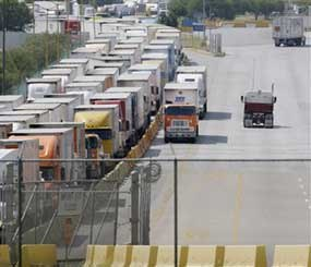 Freight trucks, center, breeze through a congested border check point using a Free and Secure Trade Lane, or FAST Lane, in Laredo, Texas, Wednesday, Oct. 14, 2009. The FAST Lane is part of the Customs-Trade Partnership Against Terrorism, or C-TPAT.