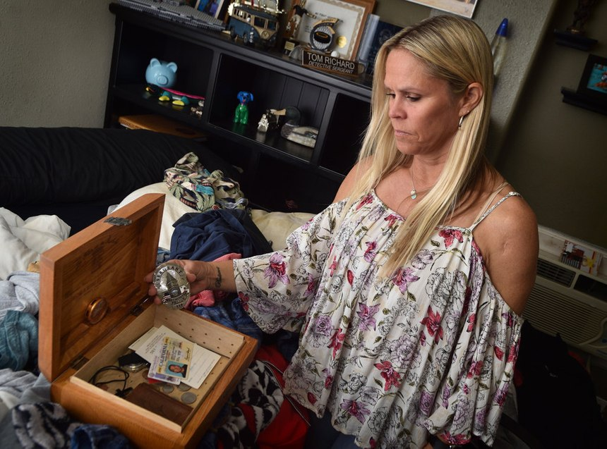 Carrie Richard goes through a box of some of her late husband's belongings, including his Westminster PD sergeant badge.