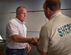 Jack Fleischli thanks OCSD SSO James Nally after receiving jewelry, held as evidence, belonging to his sister, Ginger, who was murdered in 1981. (Photo by Steven Georges/Behind the Badge)
