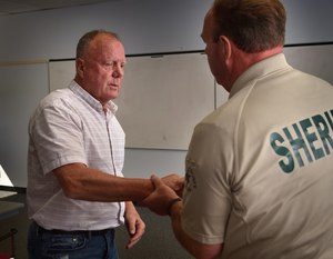 Jack Fleischli thanks OCSD SSO James Nally after receiving jewelry, held as evidence, belonging to his sister, Ginger, who was murdered in 1981.