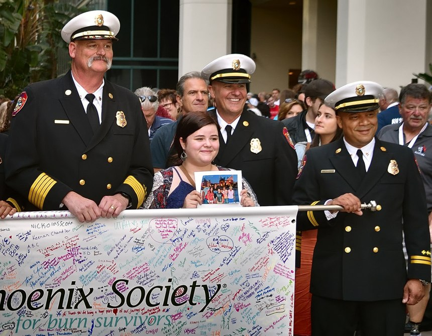 Anaheim Fire & Rescue Chief Pat Russell (left) joins others in a Walk of Remembrance on Wednesday, Oct. 2, at the Phoenix World Burn Congress outside the Anaheim Convention Center. Also pictured is burn victim Hope Henkel, holding a picture of her deceased family. (Photos/Steven Georges/Behind the Badge)