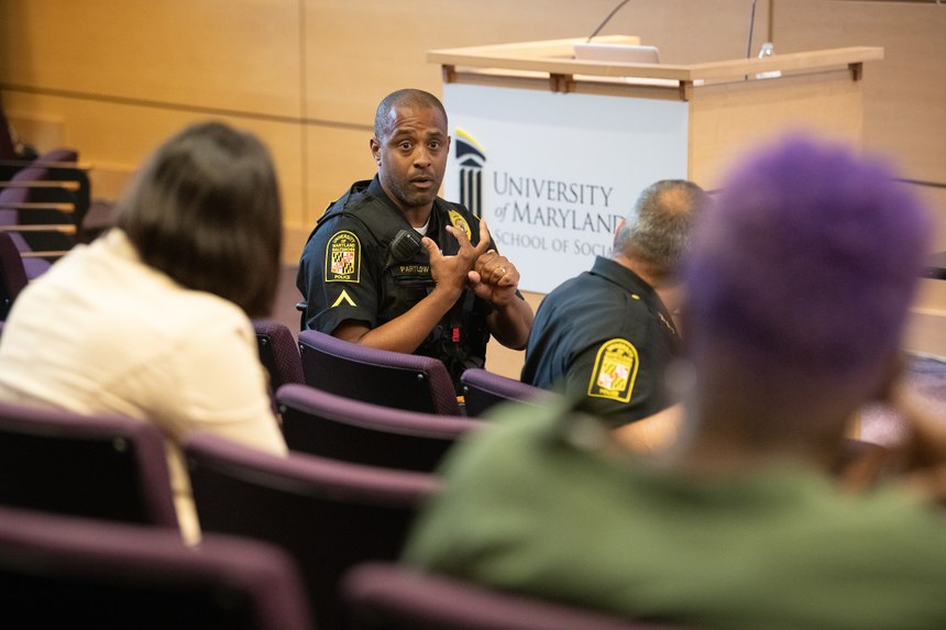 Pfc. Yale Partlow engages with the community members about new ideas for homeless outreach in Baltimore. (Photo/UMBPD)