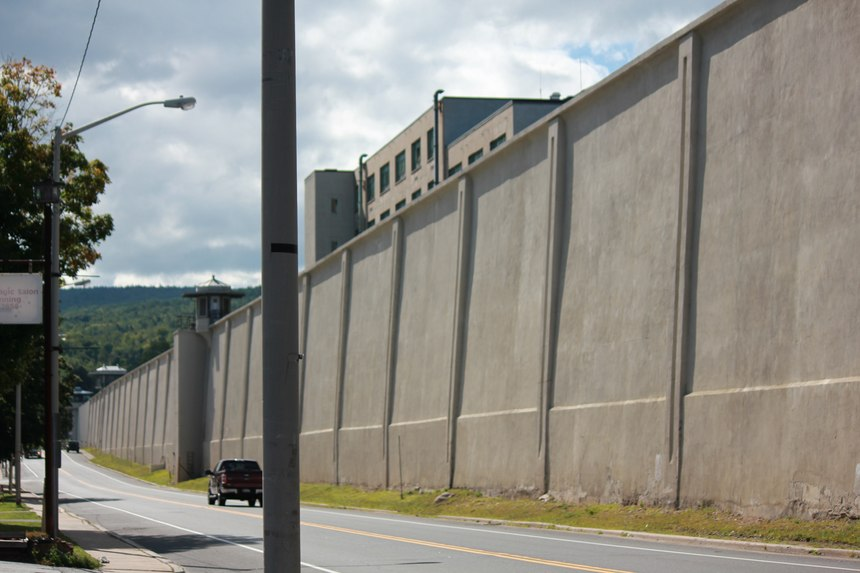The Clinton Correctional Facility perimeter wall dominates the streetscape. The tailor shop building where the convicts worked can be seen in the background.