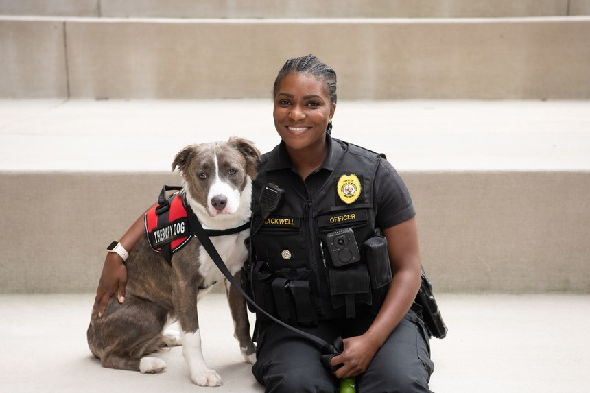 Officer Lexi poses with her human companion, UMBPD Comfort K-9 Officer Pfc. Kelli Blackwell. (Photo/UMBPD)