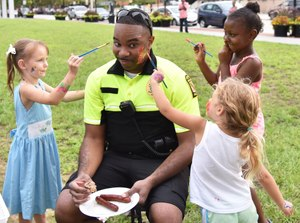 Lt. Matthew Johnson agrees to have his face painted by neighborhood children. (Photo/UMBPD)