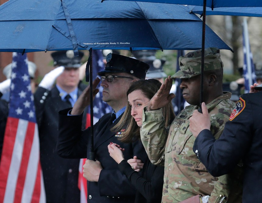 Shannon Slutman, wife of Staff Sgt. Christopher Slutman, watches as a casket containing her husband's body is moved into a funeral home in the Bronx borough of New York, Monday, April 22, 2019. Firefighters in three states are honoring the U.S. Marine and New York City firefighter who was killed by a roadside bomb in Afghanistan. (AP Photo/Seth Wenig)