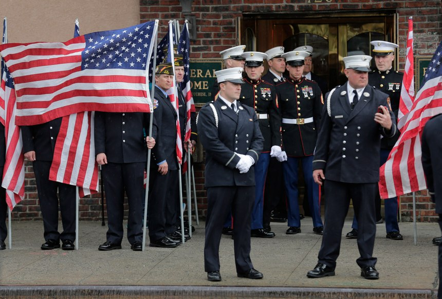 Service personnel prepare for the arrival of the body of Staff Sgt. Christopher Slutman in front of a funeral home in the Bronx borough of New York, Monday, April 22, 2019. Firefighters in three states are honoring the U.S. Marine and New York City firefighter who was killed by a roadside bomb in Afghanistan. (AP Photo/Seth Wenig)