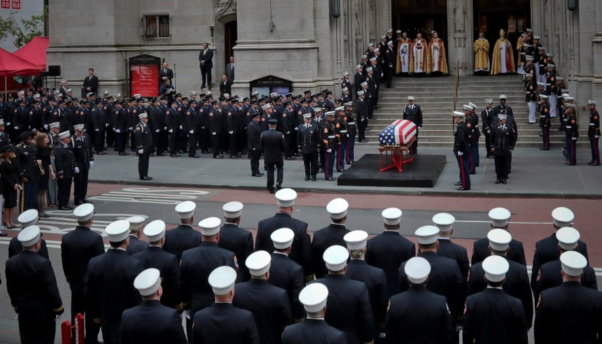 The casket of U.S. Marine Corps Staff Sergeant and FDNY Firefighter Christopher Slutman, center, arrives for his funeral service at St. Thomas Episcopal Church, Friday April 26, 2019, in New York. The father of three died April 8 near Bagram Airfield U.S military base in Afghanistan. (AP Photo/Bebeto Matthews)