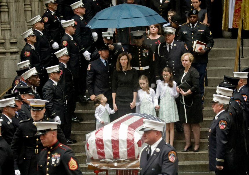 Shannon Slutman, center, stands under an umbrella, holding hands with her children as the casket for her husband, U.S. Marine Corps Staff Sergeant and FDNY Firefighter Christopher Slutman, leaves St. Thomas Episcopal Church, Friday April 26, 2019, in New York. The father of three died April 8 near Bagram Airfield U.S military base in Afghanistan.(AP Photo/Bebeto Matthews)
