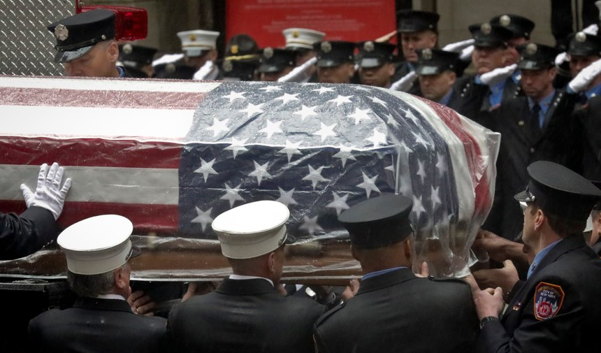 Firefighters hoist the casket of U.S. Marine Corps Staff Sergeant and FDNY Firefighter Christopher Slutman on to a firetruck, after funeral service at St. Thomas Episcopal Church, Friday April 26, 2019, in New York. (AP Photo/Bebeto Matthews)