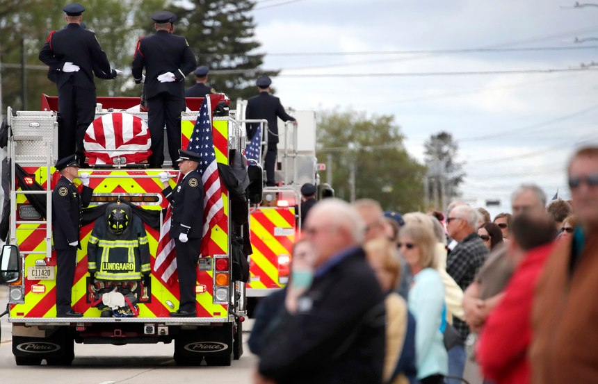 Members of the community gather along West Wisconsin Avenue during the funeral procession for Appleton firefighter Mitchell F. Lundgaard, as it makes its way toward the Appleton Alliance Church on Monday, May 20, 2019, in Appleton, Wis. The 14-year veteran of the Appleton Fire Department was fatally shot while responding to a medical emergency at the downtown Valley Transit Center on Wednesday, May 15, 2019 in Appleton, Wis.