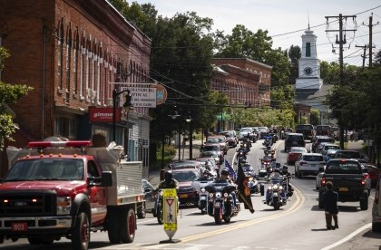 A memorial procession for Sgt. James Johnston, passes through Trumansburg, N.Y., Saturday, Aug. 31, 2019. (AP Photo/David Goldman)