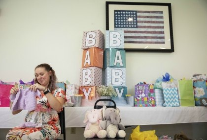 Krista Johnston opens gifts during a baby shower at the American Legion hall in Trumansburg, N.Y., Sunday, Sept. 1, 2019. (AP Photo/David Goldman)