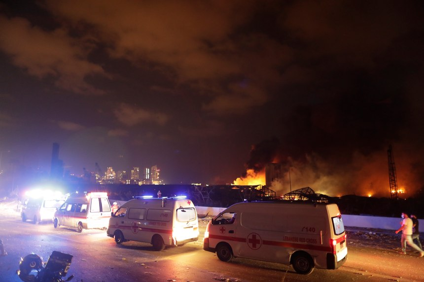 Ambulances drive past the site of a massive explosion in Beirut, Lebanon, Tuesday, Aug. 4, 2020. Massive explosions rocked downtown Beirut on Tuesday, flattening much of the port, damaging buildings and blowing out windows and doors as a giant mushroom cloud rose above the capital. Witnesses saw many people injured by flying glass and debris.