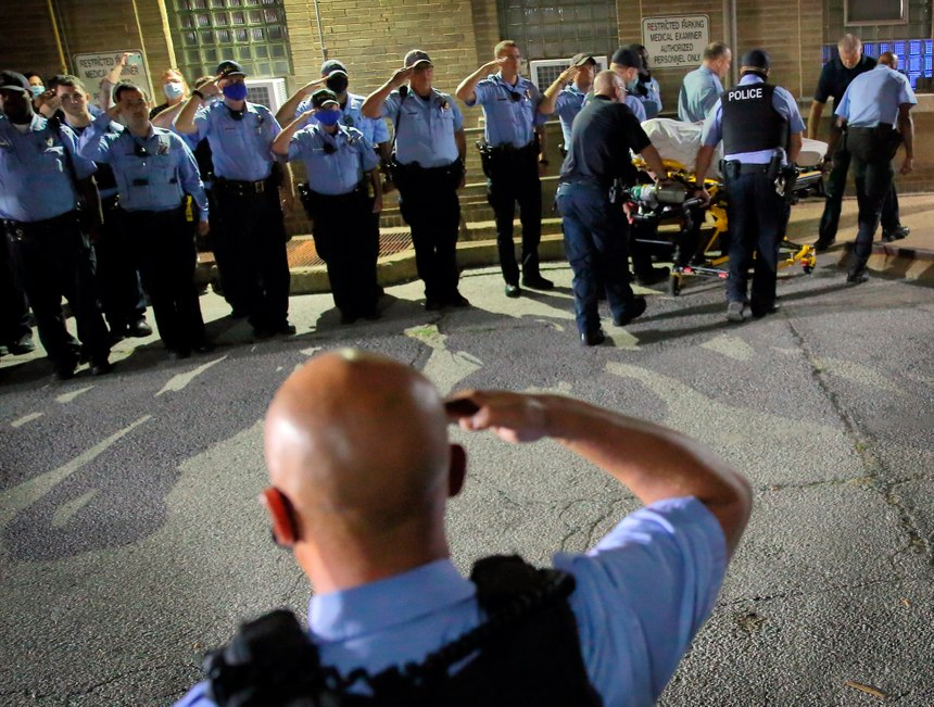 St. Louis police officers line up and salute as the body of fallen Officer Tamarris L. Bohannon is brought to the morgue in St. Louis, Sunday, Aug. 30, 2020. (David Carson/St. Louis Post-Dispatch via AP)
