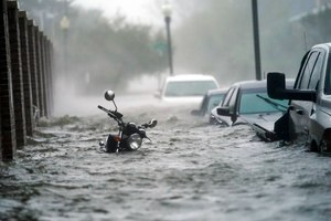 Cars and a motorcycle are are submerged in floodwaters on a street, Wednesday, Sept. 16, 2020, in Pensacola, Fla. Hurricane Sally made landfall Wednesday near Gulf Shores, Alabama, as a Category 2 storm, pushing a surge of ocean water onto the coast and dumping torrential rain that forecasters said would cause dangerous flooding from the Florida Panhandle to Mississippi and well inland in the days ahead. (AP Photo/Gerald Herbert)