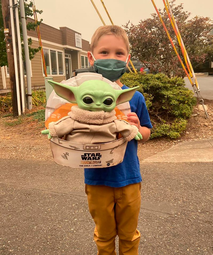 "Five-year-old Carver holds up a Baby Yoda toy on Saturday, Sept. 12, 2020 in Scappoose, Oregon. Carver donated the toy to Oregon firefighters, who have been having fun posing the tiny green Force user on the fire lines since. Baby Yoda has traveled between fire crews across the Western United States, with his adventures documented on the Facebook page ""Baby Yoda fights fires."""