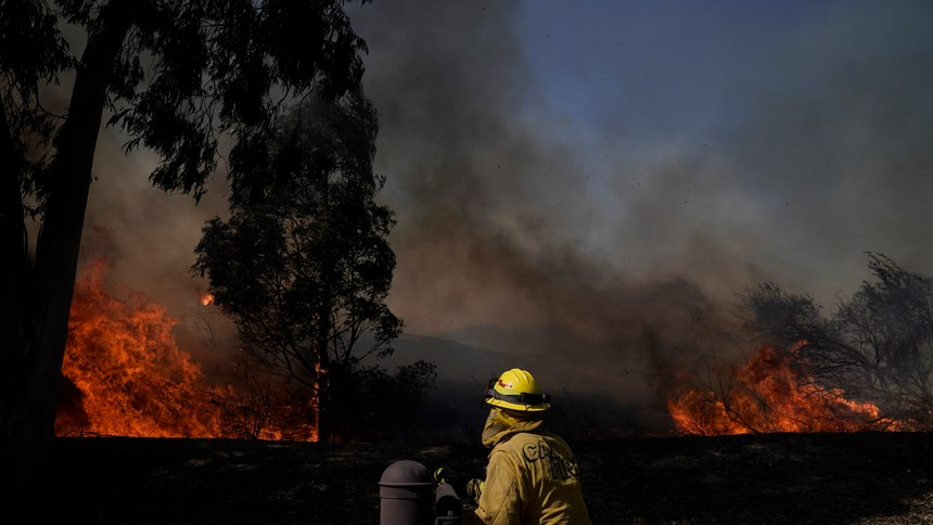 A firefighter watches flames from the Silverado Fire, Monday, Oct. 26, 2020, in Irvine, Calif. A fast-moving wildfire forced evacuation orders for 60,000 people in Southern California on Monday as powerful winds across the state prompted power to be cut to hundreds of thousands to prevent utility equipment from sparking new blazes.
