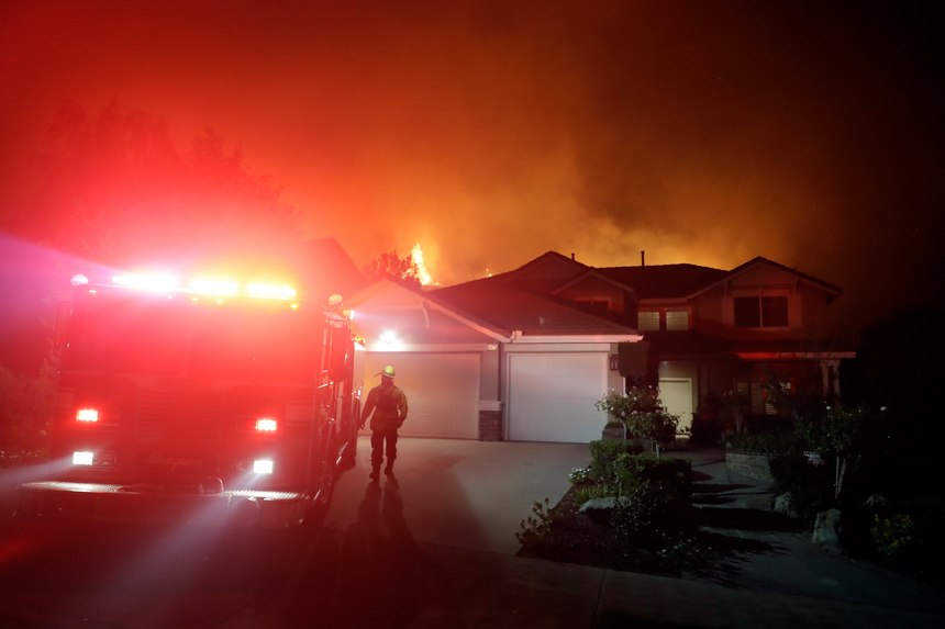 A firefighter walks next to an engine as crews make a stand in front of an advancing wildfire in a residential neighborhood Friday, Nov. 9, 2018, in West Hills, Calif.