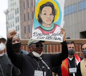 Kevin Peterson, founder and executive director of the New Democracy Coalition, displays a placard showing Kentucky EMT Breonna Taylor as he addresses a rally in Boston. One of the officers involved in Taylor's fatal shooting, Brett Hankison, has been fired, officials announced Friday.