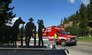 A western-themed mailbox sign is shown at left as a paramedic unit from King County's Medic One stands by on Twisp River Road in Twisp, Wash.