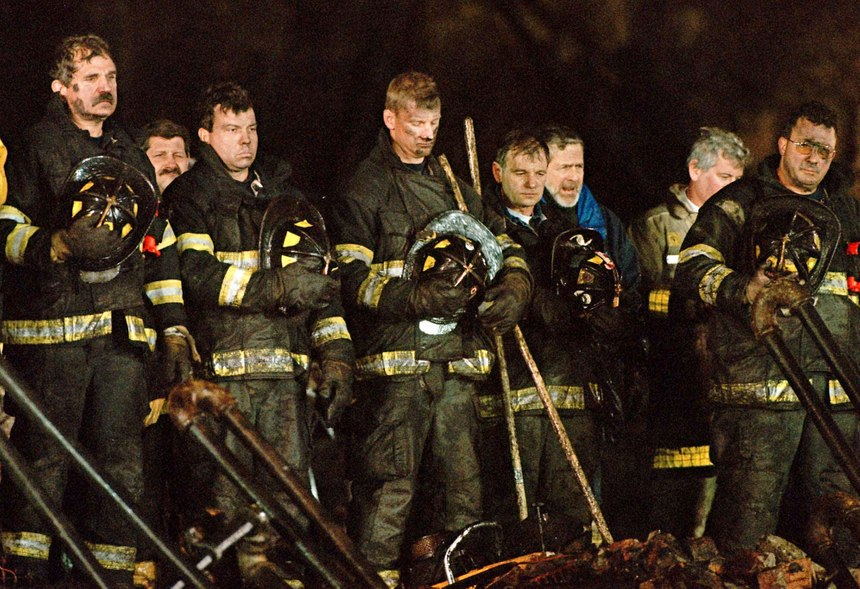 Firefighters stand for a moment of silence on Dec. 10, 1999, at 6:13 p.m. exactly one week after the first alarm sounded for the Worcester Cold Storage and Warehouse Co. building fire, which killed six firefighters in Worcester Mass. (AP Photo/Paul Kapteyn Worcester Telegram & Gazette)