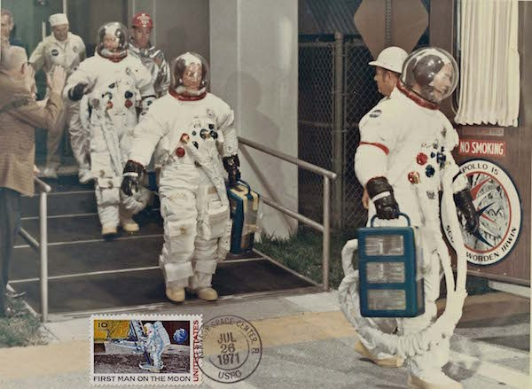 Astronaut Rescueman Bill Killen escorts Apollo 15 crewmembers from their quarters in the Manned Spacecraft Operations Building en route to Launch Complex 39. This NASA photograph is unique in that it shows a 10 cent Moon Landing Stamp and was hand-canceled at the Kennedy Space Center Post Office shortly after liftoff. (Photo/NASA-Bill Killen Collection)