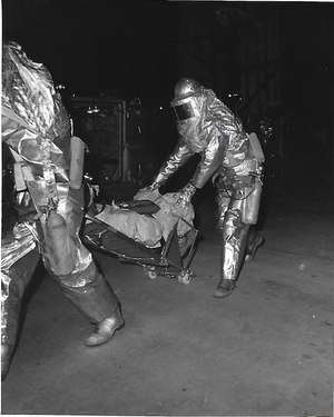 After practicing rescue of a fill-in astronaut, astronaut rescuemen move the subject to an M-113 personnel carrier parked at the base of the mobile launcher. Waiting at the M-113 is a Department of Defense medic with the equipment and medical skills to attend the flight crewmember. The Astronaut Rescue team practiced procedures that would be used in the event of a real emergency prior to the launch of Apollo 17.