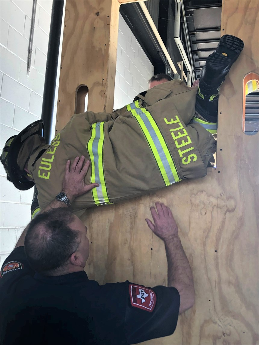 A captain works with a new firefighter on bailout procedures. Good training builds trust and confidence at all levels.