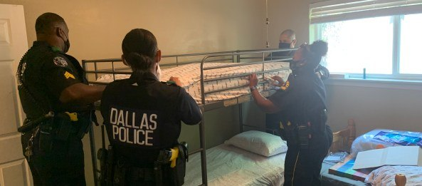 Dallas police officers, including McIntyre and Pesina, help assemble bunk beds for the family.