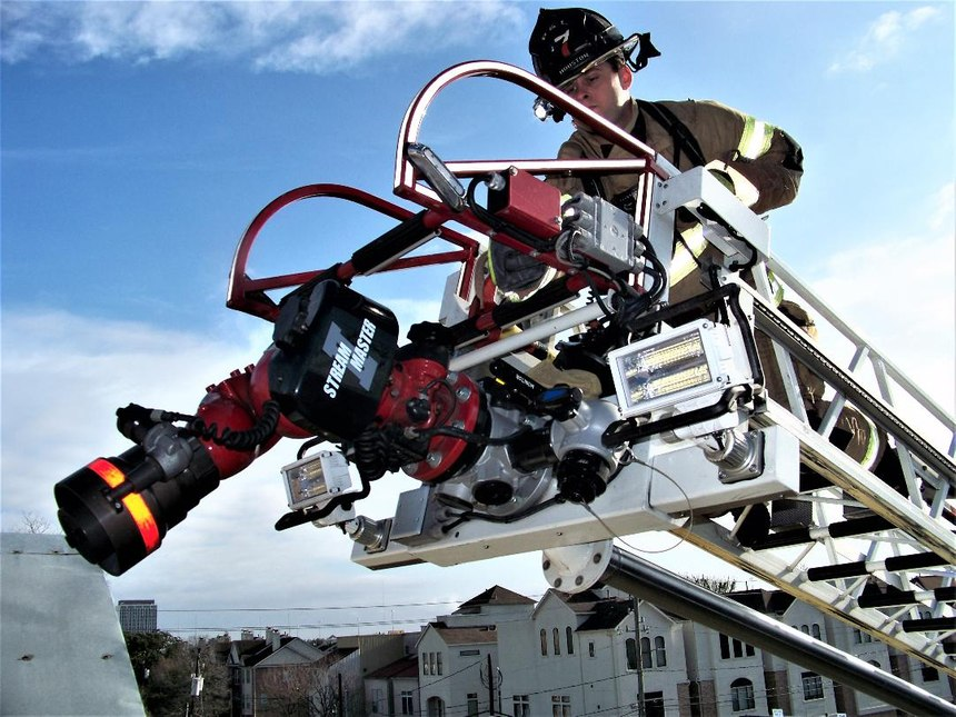 It is absolutely safe to assign firefighters to the tip of the ladder during aerial master stream operations. Most aerials are rated for 500 pounds while flowing water. It is also acceptable to raise lower and rotate while a firefighter is on the tip. Such operations will typically be slow movements.