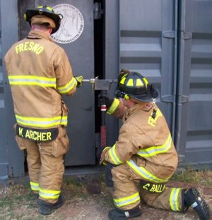 Figure 11: When a two-person team is being utilized, it is imperative that the firefighter swinging the axe takes a kneeling position.