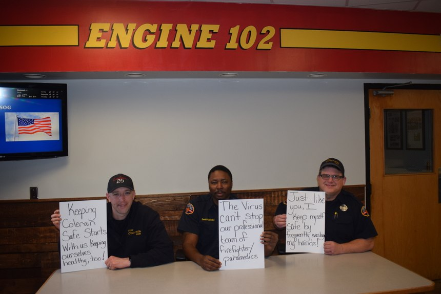 Post photos of firefighters at the station holding signs that indicate they are practicing social distancing for good health. (Photo/Robert Rielage)