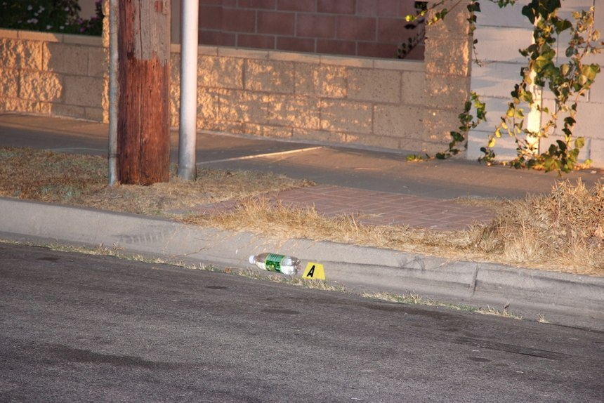 A crime scene photo showing the starting location of the incident. Note the skid mark in the street and the bottle in the gutter. Photo courtesy of Anaheim City Attorney's Office.