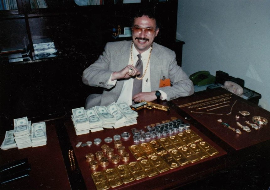 Javier poses with gold and stacks of cash seized from an Escobar safe house in Medellin during the Escobar manhunt. (Photo/Gary Sheridan)