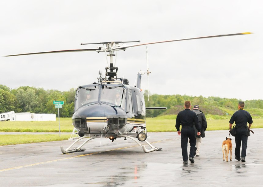 Law enforcement officers escort a police canine to a helicopter for a training exercise that will familiarize canines with the experience of being airborne on June 13, 2019 at the State Preparedness Training Center in Oriskany. [JOLENE CLEAVER / OBSERVER-DISPATCH]