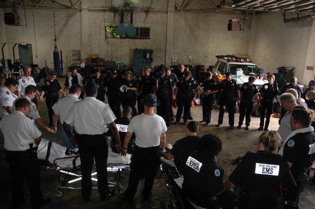 New Orleans Emergency Medical Services (formerly known as the New Orleans Health Department) professionals gather in prayer prior to assuming their post to await Hurricane Katrina landfall. (Photo/Miles Jeffery Watts, Jr.)