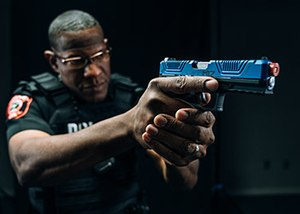 officer with blue Laser Shot simulated weapon