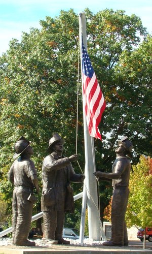 """A bronze monument, named """"To Lift a Nation,"""" recreates the famous photo taken by Thomas E. Franklin, a photographer for the Bergen Record, who captured the image of three firefighters raising the American flag at Ground Zero."""