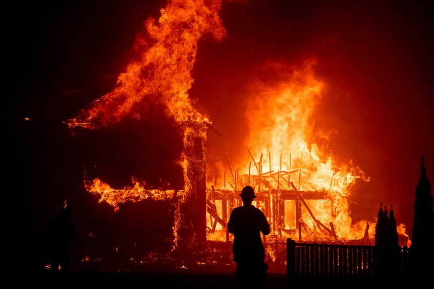 A home burns as the Camp Fire rages through Paradise, California in November 2018. (AP Photo/Noah Berger)