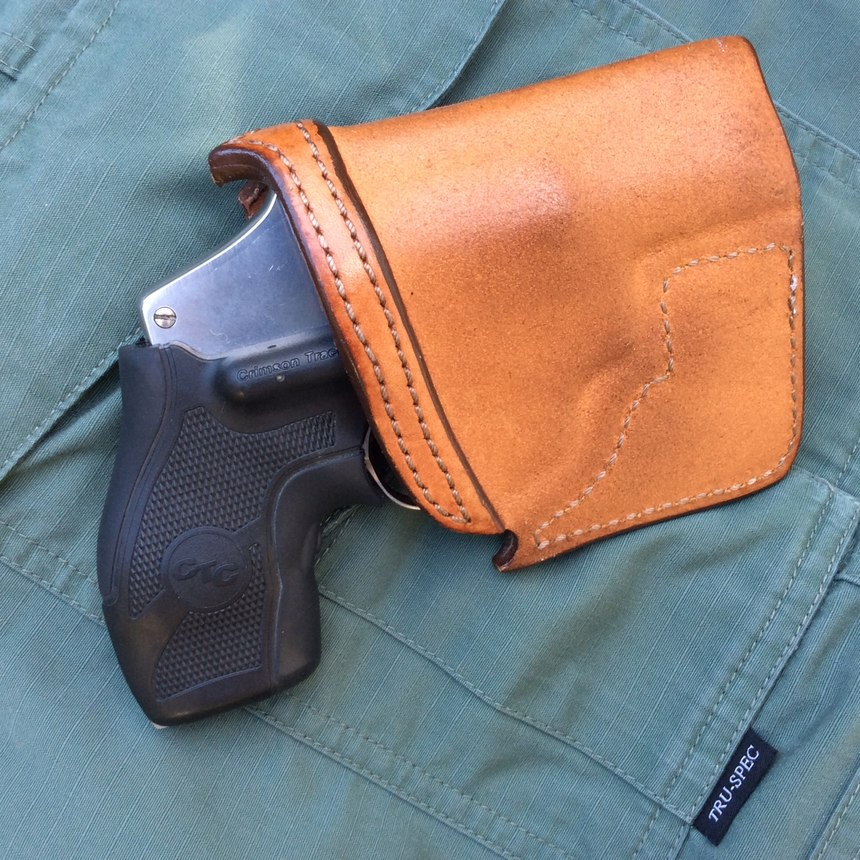 "A holster is an absolute necessity for a snubby carried in a pants pocket. It will keep the gun oriented properly for the draw, break up its outline and protect the gun from damage and debris. The Crimson Trace LaserGrips on this example are an excellent addition to a BUG that might have to be fired from awkward or ""broken"" shooting positions. (Photo/Mike Wood)"