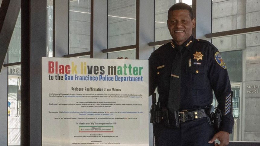 San Francisco Chief of Police Bill Scott stands with a 'Black lives matter' poster.