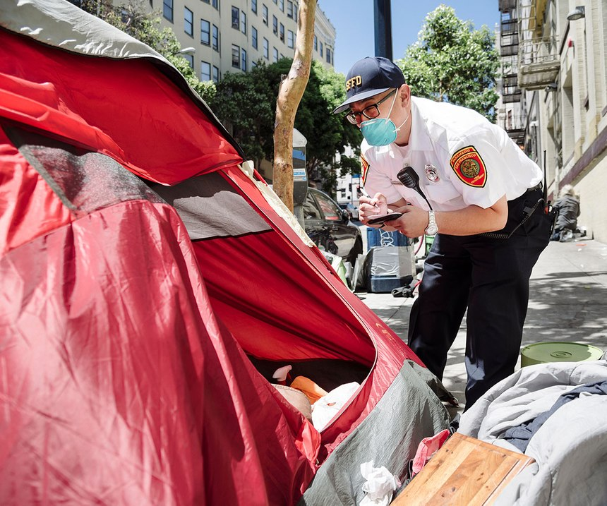 San Francisco Fire Department Captain Dan Nazzareta, a community paramedic, writes down information provided by people staying in a tent in the city's Tenderloin district in order to help them relocate to a shelter