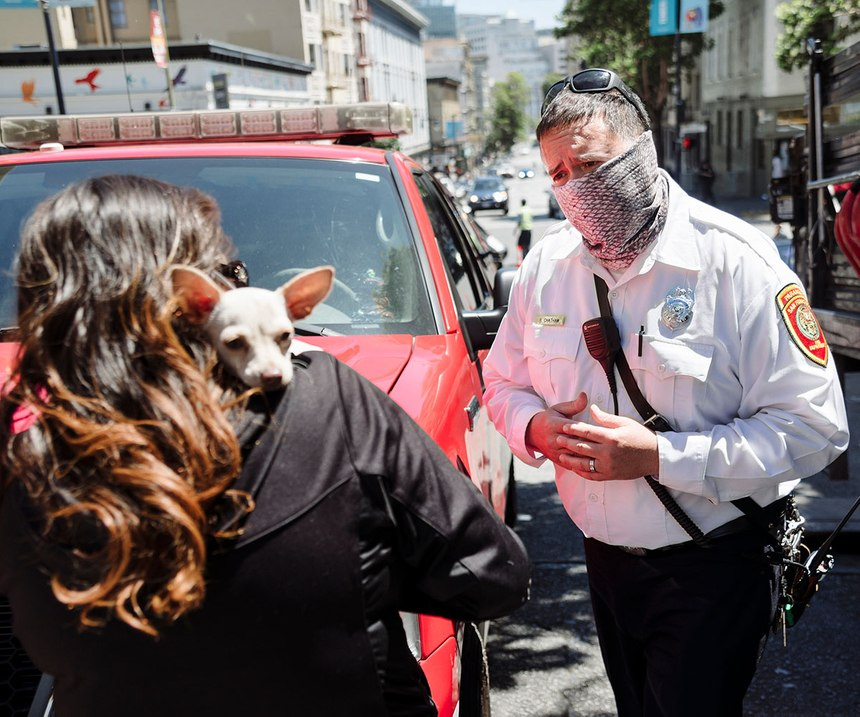 San Francisco Fire Department Captain Brandon Chatham, a community paramedic, talks about shelter options with a woman experiencing homelessness in the city's Tenderloin district
