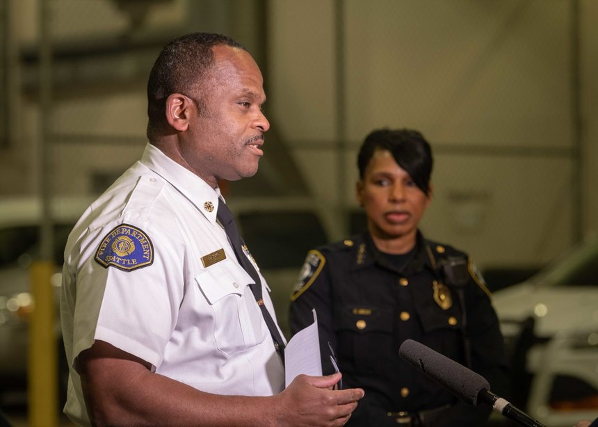 Fire Chief Harold Scoggins speaks to the media, with Police Chief Carmen Best standing by.