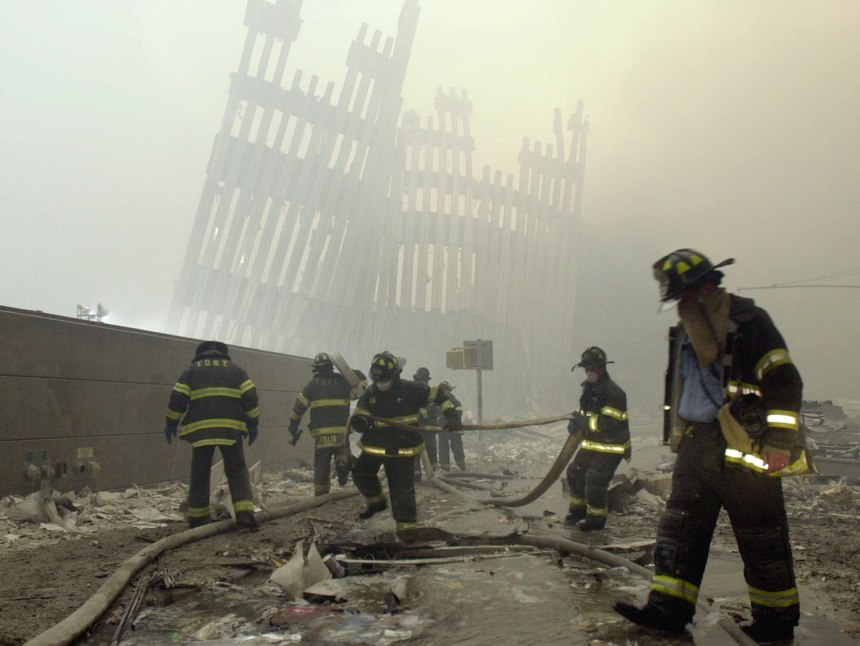 With the skeleton of the World Trade Center twin towers in the background, FDNY firefighters work amid debris on Cortlandt St. after the terrorist attacks of Tuesday, Sept. 11, 2001. (AP Photo/Mark Lennihan)