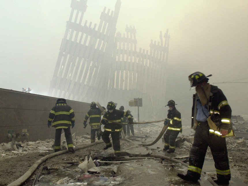 With the skeleton of the World Trade Center twin towers in the background, FDNY firefighters work amid debris on Cortlandt St. after the terrorist attacks of Tuesday, Sept. 11, 2001.