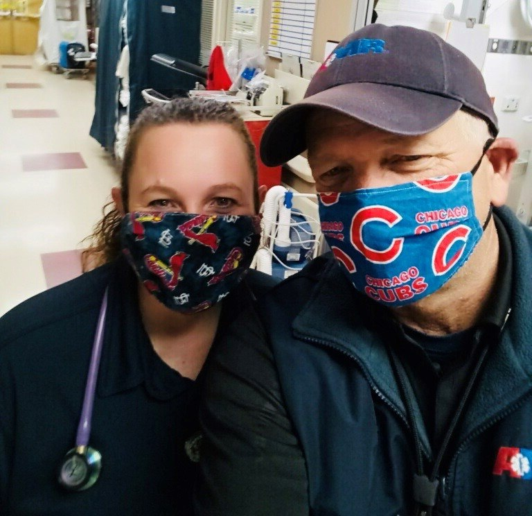 AMR EMT Stephanie Hatfield and Paramedic John Claspell wearing their baseball masks at the emergency department after dropping off a patient.