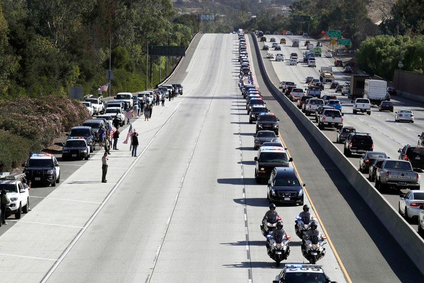 A law enforcement motorcade, providing an escort for a hearse carrying the body of Sgt. Ron Helus, makes its way northbound on Highway 101 Thursday, Nov. 8, 2018, in Newbury Park, Calif. Helus was fatally shot while responding to a mass shooting at a country music bar in Southern California.